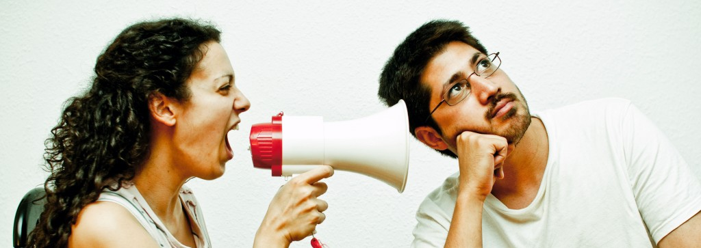 Woman using a megaphone to yell at a man